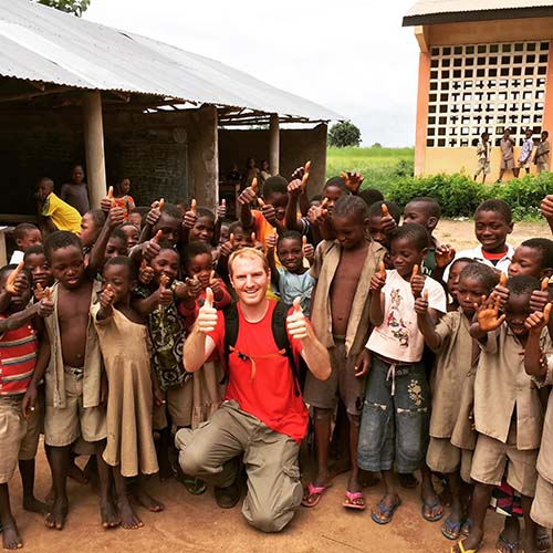 Clark Young traveling abroad with smiling children in village